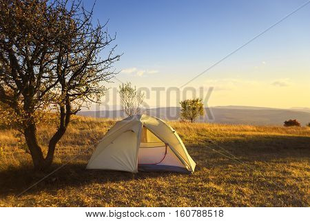 Camp tent stands in the meadow near the tree with light of the rising sun passing through it at autumn landscape background with mountains at the horizon.