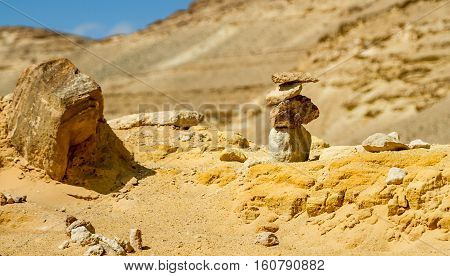 Desert landscape pyramid of rough stones on foreground in Negev desert Israel