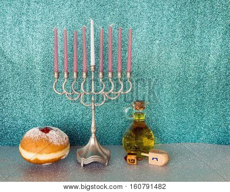 Jewish menorah with candles, sweet donuts wooden dreidels and jar of olive oil are traditional symbols for Hanukkah holiday