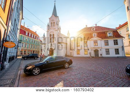 Riga, Latvia - September 22, 2016: View on the roman catholic church with luxury car on the square in the old town of Riga, Latvia