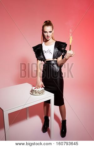 Young beautiful brutal blonde girl in black leather skirt push hand in cake holding sparkler over pink background.