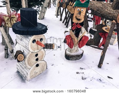 Vintage Christmas Village Cute Snowman, Caroller and Red Nosed Reindeer made of wood outdoors on a white Christmas market day in fresh snow Card or background with copy space
