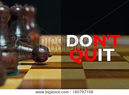 Chess figures on table with Motivational message Don't Quit
