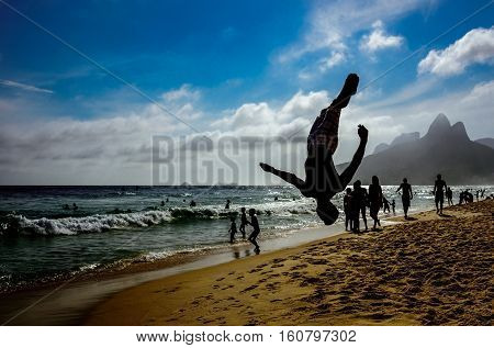Silhouette of the man performing a back somersault at Ipanema beach with silhouettes of swimming and walking people, blue sky with white clouds and Dois Irmaos Mountain at the background, Rio de Janeiro, Brazil
