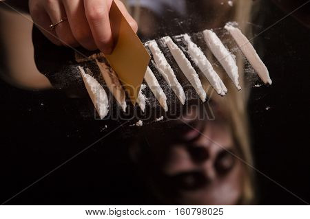 cocaine or other drugs cut with card on mirror with female reflection, hand dividing white powder narcotic