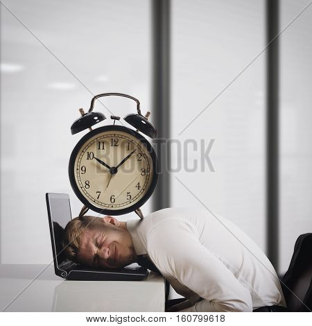Businessman on laptop with a big alarm clock on head. Oppressed by deadlines concept
