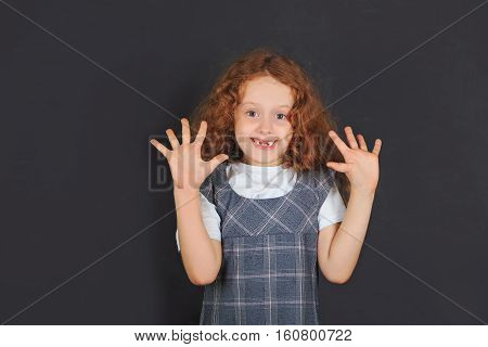 Laughing toothless school girl showing open palm. Easy learning excellent education concept.