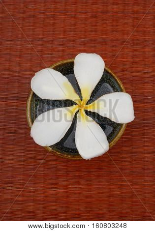 frangipani flower with stones in bowl on mat