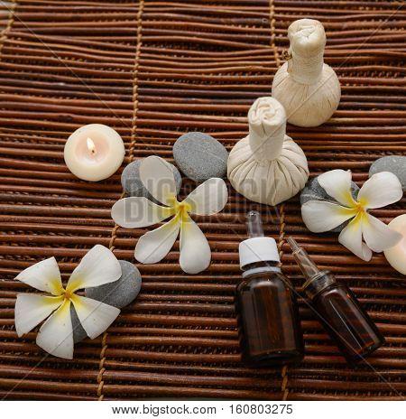 frangipani with massage oil and massage ball ,stones, on mat