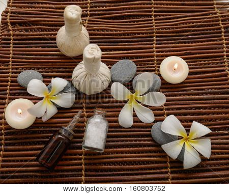 frangipani with massage oil and massage ball ,stones,oil,  on mat