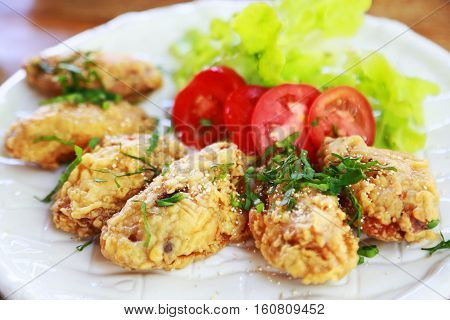 fried chicken wings or fried chicken with vegetable and sauce on white dish. fried chicken is bad cholesterol and bad for health when eating a lot. fast food for who work in city or office.