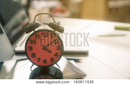 Time to go home. The alarm clock counting at the end of the day on an office table.