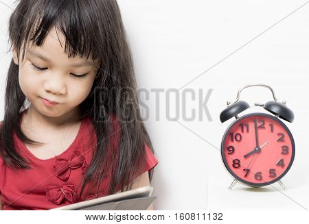 Kid Study time, Asian girl is reading a book with a clock timing her study time.