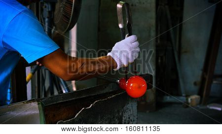 Man Craft wearing white glove forming on Hot Glass
