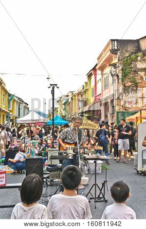 PHUKET THAILAND SEPTEMBER 27: Street artist musician entertains tourists at the walking street among old building Chino Portuguese style on street of Phuket town Thailand on September 27 2016.