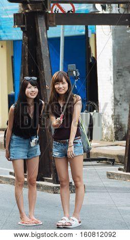 PHUKET THAILAND SEPTEMBER 27: Tourists selfie at the walking street among old building Chino Portuguese style street of Phuket town in Phuket Thailand on September 27 2016.