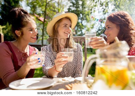 friendship, holidays, celebration, people and food concept - happy women or friends having party at summer garden