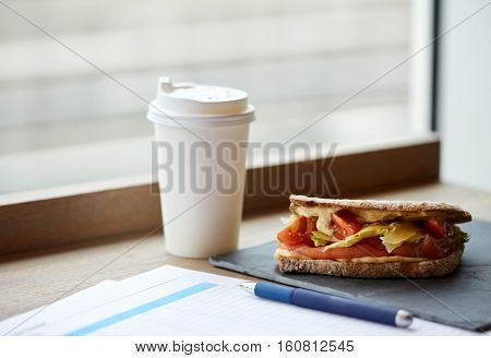 business lunch, food, dinner and eating concept - salmon panini sandwich with tomatoes and cheese, cup of drink and papers on cafe table