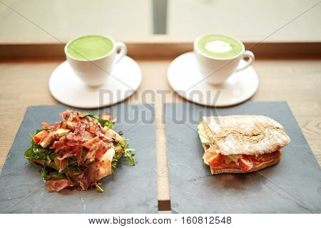 food, dinner, haute cuisine and eating concept - prosciutto ham salad with salmon panini sandwich on stone plates and cups of matcha green tea latte at restaurant