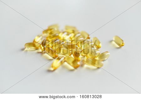 medicine, drugs, healthcare, food supplements and pharmaceutics concept - cod liver oil or omega 3 gel capsules