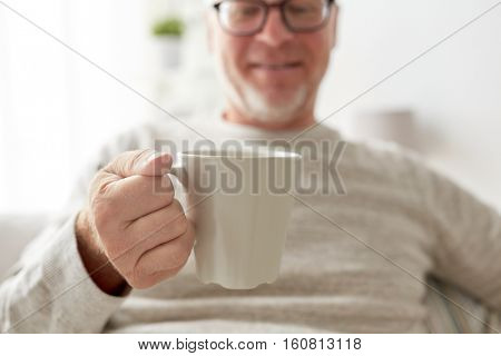old age, drink and people concept - happy senior man with cup of tea or coffee at home