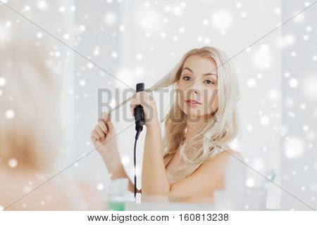 beauty, hairstyle, morning and people concept - smiling young woman with styling iron straightening her hair and looking to mirror at home bathroom over snow