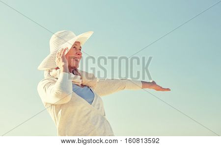 age, leisure and people concept - happy senior woman in sun hat over blue sky