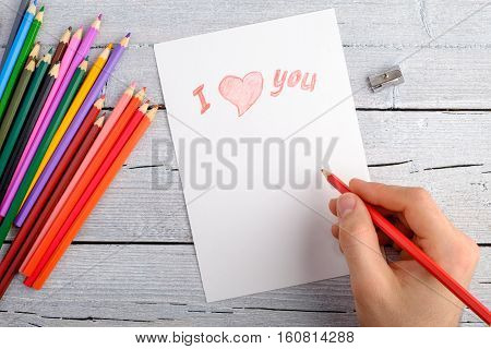 drawing with colored pencils postcard for Valentine's day right-hand on white paper on white wooden background copy space for text top view.