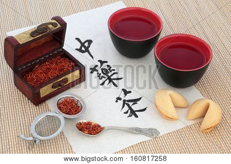 Chinese safflower herbal tea with calligraphy on rice paper, tea cup, old wooden caddy box and strainer also used in alternative herbal medicine. Translation reads as chinese herb tea.