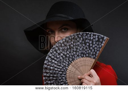 The beautiful young woman in a black wide-brimmed hat and a dress of scarlet color with a dark fan in a hand
