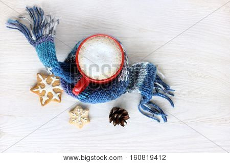 frothy coffee in cozy scarf with ginger cookies and pine cones / delicious winter vacation