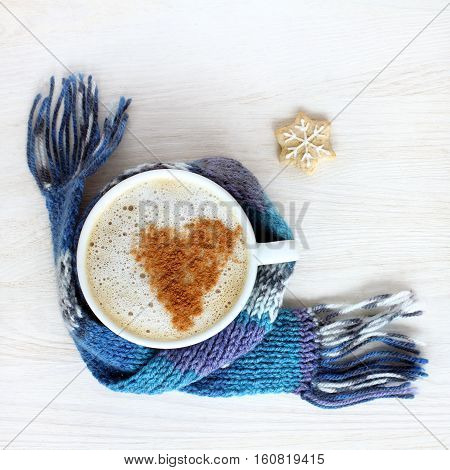heart symbol of grated cinnamon in a mug with a frothy coffee top view / favorite warming drink