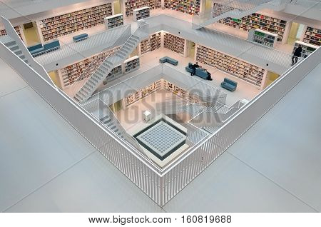 Stuttgart, Germany - April 16, 2015: Interior of modern library in Stuttgart. White floors with bookshelves connected with stairs. Look down. View from the corner.