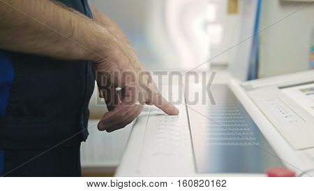 Industrial Worker. Man using industrial control panel of the Printing machine, close up