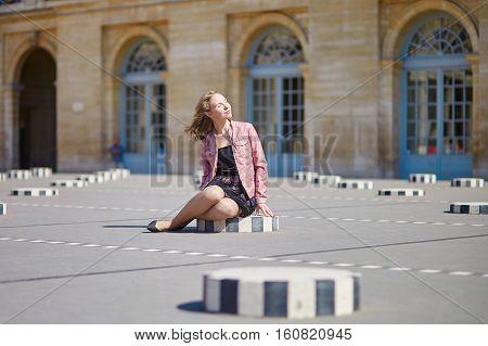Woman Sitting On One Of The Colonnes De Buren In Paris