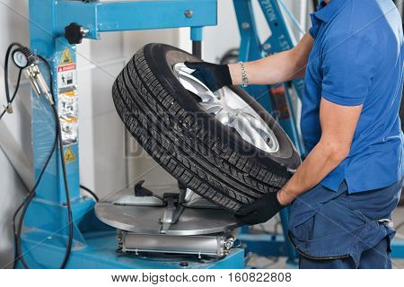 Mechanic removes car tire closeup. Machine for removing rubber from the wheel disc.