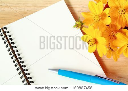 Open blank spiral note book and yellow flower on wood background.