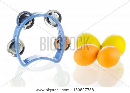 Tambourine and egg maracas shaker on a white background.
