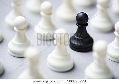 Single Black Chess Piece Amongst White Ones