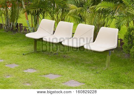 Four empty chairs oon lush green lawn with trees in a park.