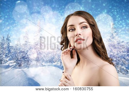 Portrait of young woman fae with cream over winter forest background.