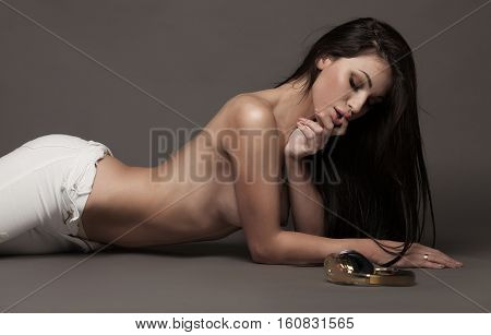 Sexy fit naked woman with healthy clean skin in white jeans lying down, on grey background. Headphones near model.