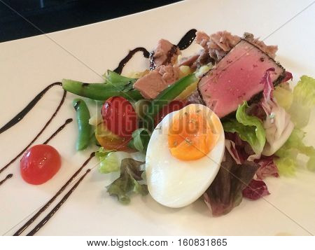 Close-up healthy grill medium rare tuna and egg salad top with balsamic vinegar salad dressing