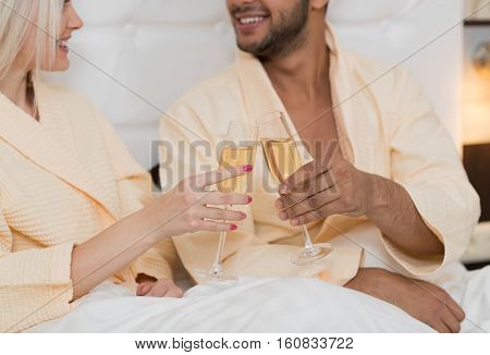 Young Couple Lying In Hotel Bed Drink Champange, Happy Hispanic Man And Woman Closeup Lovers In Bedroom