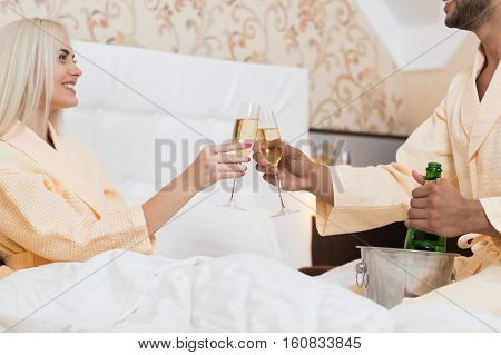 Young Couple Lying In Hotel Bed Drink Champange, Happy Smile Hispanic Man And Woman Lovers In Bedroom