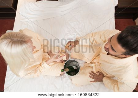Young Couple In Hotel Bed Drink Champange, Hispanic Man And Woman Lovers In Bedroom Top Angle View