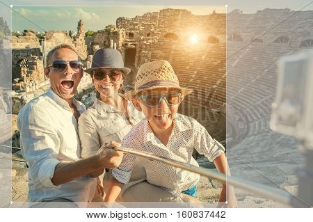 Young positive famly take a vacation photo on the Side ampitheatre view