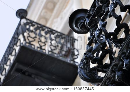 Looking up at old black wrought iron balcony closeup. Selective focus.