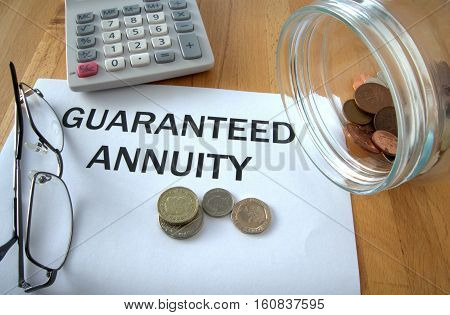 Guaranteed Annuity with coins on paper and in pot and calculator behind