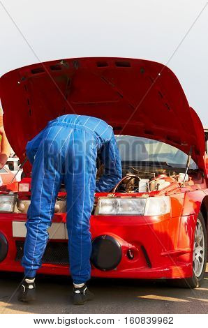 A mechanic in blue overalls repairs a red racing car